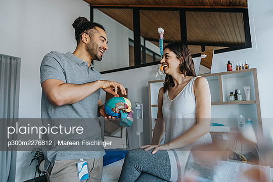 Smiling male physical therapist explaining skull model to female patient in practice - p300m2276812 by Mareen Fischinger