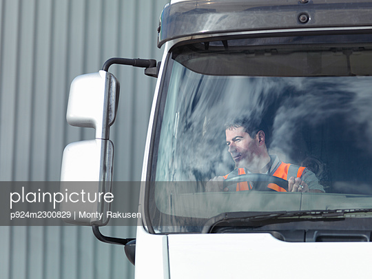 UK, Truck driver looking at side view mirror - p924m2300829 by Monty Rakusen