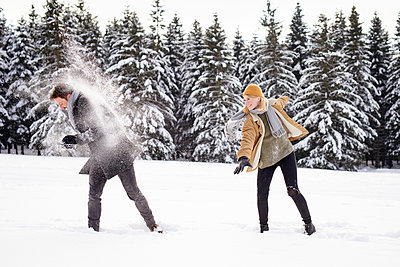 Young couple having a snowball fight - p1124m1589319 by Willing-Holtz