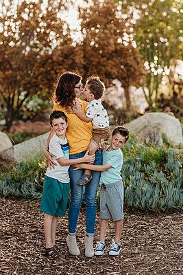 Portrait of mother kissing son with boys hugging her in sunny garden - p1166m2136613 by Cavan Images