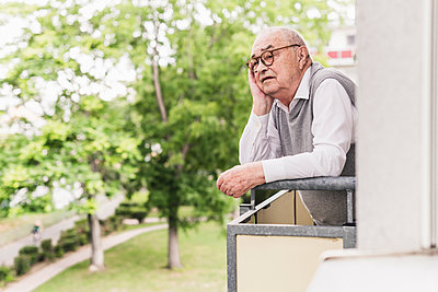 Portrait of senior man standing on balcony looking at distance - p300m2189172 by Uwe Umstätter
