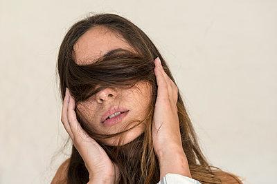Frau mit Haarsträhnen vor ihren Augen - p427m1195212 von Ralf Mohr
