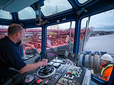 Worker driving tugboat in wheelhouse - p429m747062f by Monty Rakusen