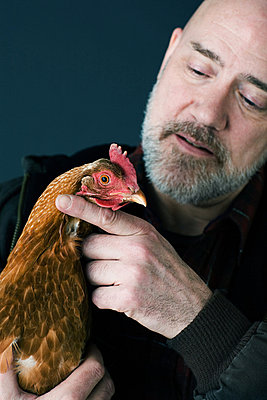 Man holding a chicken - p9246409f by Image Source