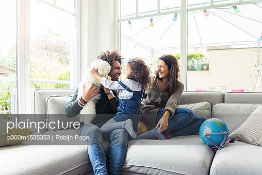 plainpicture | Photo library for authentic images - plainpicture p300m1535353 - Happy family with dog sitti... - plainpicture/Westend61/Robijn Page