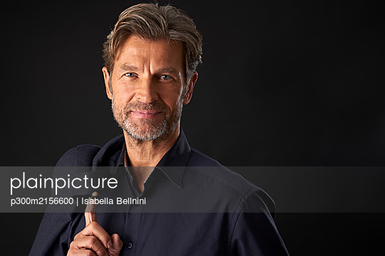 Portrait of smiling mature businessman against dark background - p300m2156600 by Isabella Bellnini