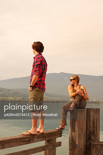Young couple looking out from pier, Lake Annecy, Annecy, Rhone-Alpes, France - p429m2074412 by Ross Woodhall