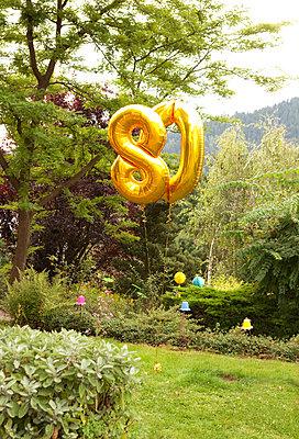 Dekoration for 80th birthday in garden with golden balloons - p300m1205698 by Michelle Fraikin