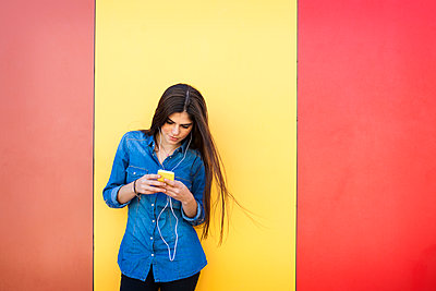 Young woman with earphones and smartphone standing in front of colourful wall - p300m1416513 by Valentina Barreto
