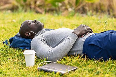 Businessman lying on a meadow listening music with earphones and laptop - p300m2104055 von Javier Sánchez Mingorance