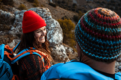 Happy girlfriend looking at boyfriend while hiking on mountain during vacation - p300m2241083 by Rafa Cortés