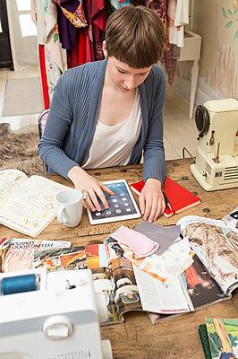 Female fashion designer using digital tablet at her work desk - p300m998420f by Dieter Schewig