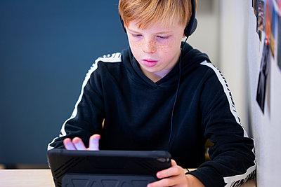 Boy using digital tablet in classroom - p312m2174469 by Scandinav