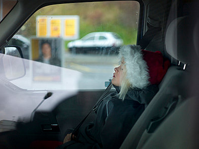 Girl wearing santa hat napping inside car - p528m713833 by Johan Willner