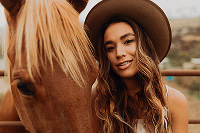 Young woman in felt hat next to horse, close up portrait, Jalama, California, USA - p924m2068255 by Peter Amend