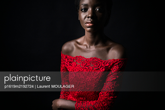 Portrait of a young black woman with red dress looking at the camera - p1619m2192724 by Laurent MOULAGER