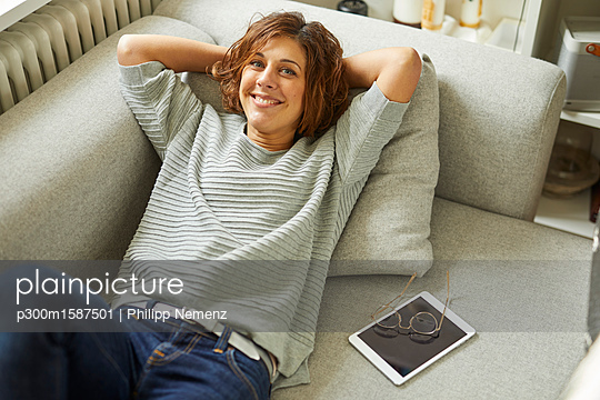 Portrait of smiling mature woman relaxing on couch - p300m1587501 von Philipp Nemenz