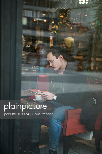 Young man sitting in a cafe - p352m2121174 by Folio Images