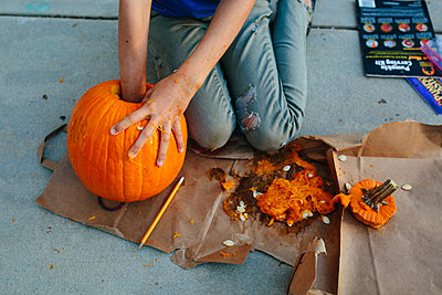 Girl reaches into pumpkin to remove insides with other hand messy - p1166m2078352 by Cavan Images