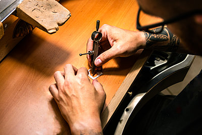 Men's hands in a jewelery workshop marking silver piece with compass - p1166m2285744 by Cavan Images