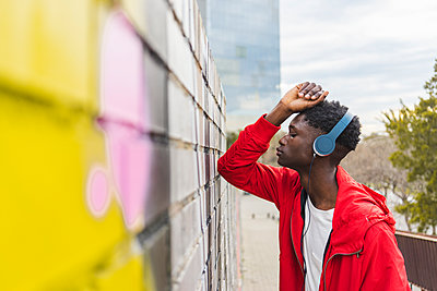 Young black man leaning on wall, listening music with headphones - p300m2059787 by VITTA GALLERY