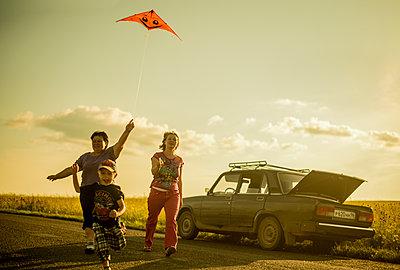 Caucasian family flying kite on rural road - p555m1418705 by Aleksander Rubtsov