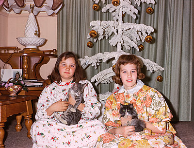 Portrait of Caucasian sisters wearing pajamas holding cats on Christmas - p555m1444198 by PBNJ Productions