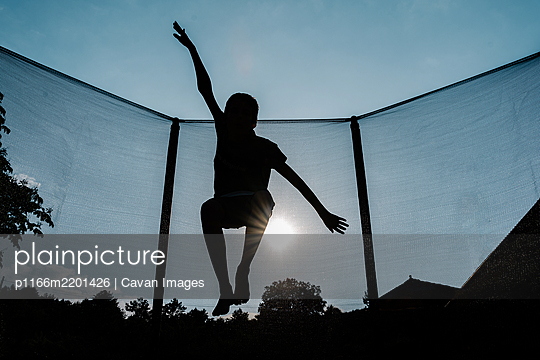 horizontal front backlighting photo of a silhouette of a barefoot young boy jumping or flying on a trampoline with net and the sun at the background reflecting sunbeam rays on his shadow - p1166m2201426 by Cavan Images