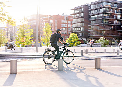 Bicycle courier riding an electric bike - p1124m2052989 by Willing-Holtz