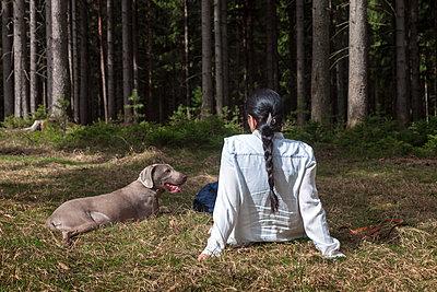 Frau mit Hund in einer Waldlichtung - p1168m1563599 von Thomas Günther