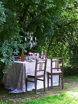 Dark wood chairs at table with tablecloth in garden - p1183m995939 by Ranek, Lars