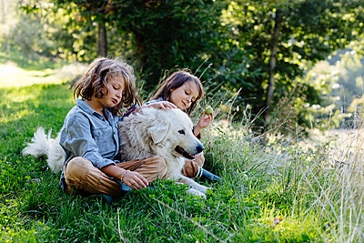 Two kids relaxing with dog on a meadow - p300m2144759 by Sofie Delauw
