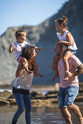 Cheerful parents with kids on shoulder enjoying at beach - p300m2257255 by SERGIO NIEVAS