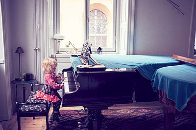 Little girl playing piano in living room - p312m1522212 by Dan Lepp