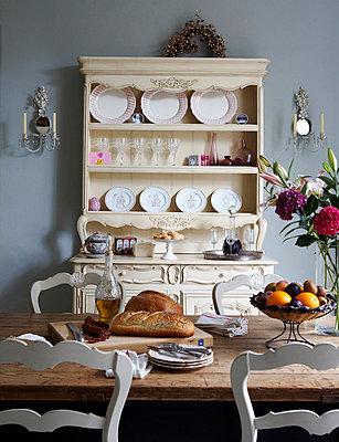 Roger Lascelles clock beside window above vegetables in Georgian townhouse kitchen - p349m789883 by Brent Darby