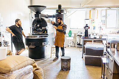 Two men having a conversation over a coffee roasting machine in Sweden - p352m2041222 by Folio Images