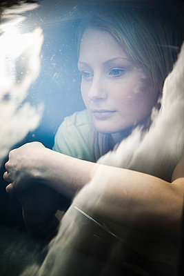 Young woman sitting in her car - p4130387 by Tuomas Marttila