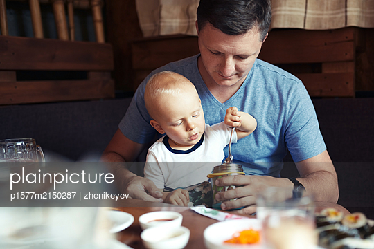 Cute boy sitting on his father knees while eating - p1577m2150287 by zhenikeyev