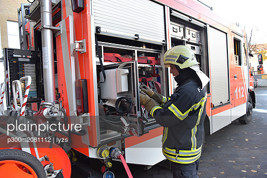 Firefighter standing at fire engine - p300m2081112 by lyzs