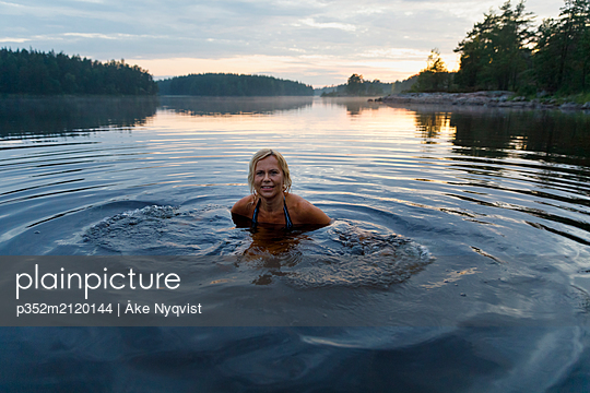Woman in Lake Skiren at sunset in Sweden - p352m2120144 by Åke Nyqvist