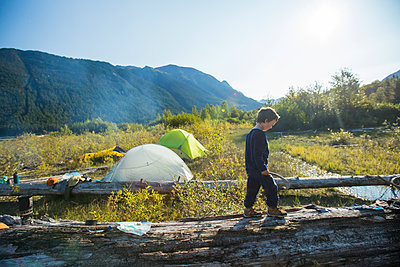 Young boy balancing on fallen log near wilderness campsite, Canada. - p1166m2212569 by Cavan Images