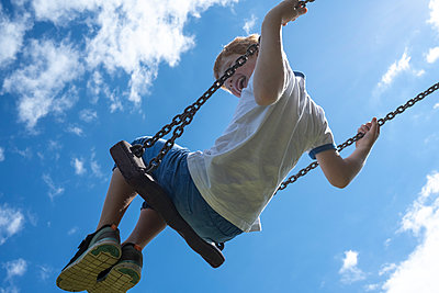 Laughing child in a swing - p236m2196624 by tranquillium