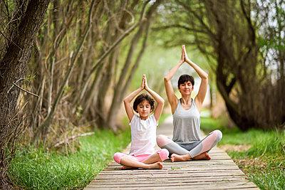 Mother and daughter doing yoga on boardwalk - p300m1587756 von Javier Sánchez Mingorance