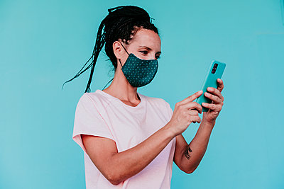 Woman wearing protective face mask using smart phone against turquoise background - p300m2220823 by Eva Blanco