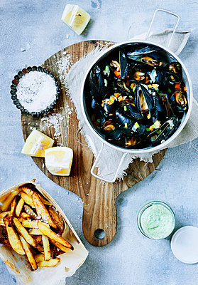 Platter of steamed mussels and fries - p429m746985f by Line Klein