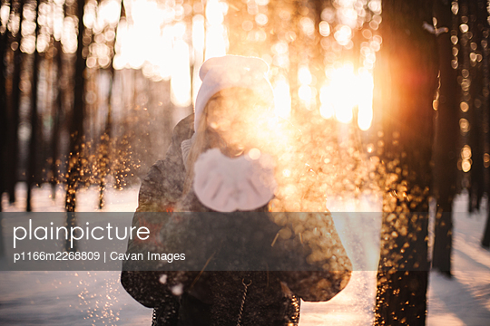 Woman blowing snow standing in park at sunset during winter - p1166m2268809 by Cavan Images