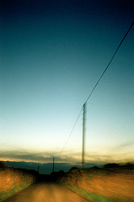 Blurred image of road at night with telegraph poles - p1047m953675 by Sally Mundy