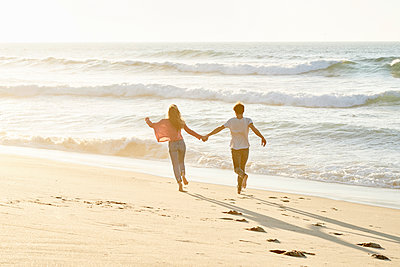 Young couple running on beach - p1124m1508616 by Willing-Holtz