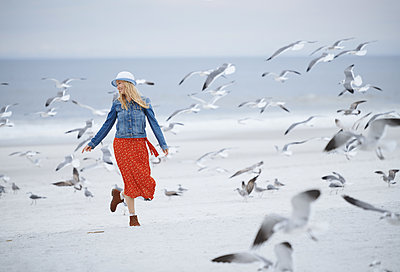 Woman running next to the ocean surrounded by flying seagulls - p1577m2150317 by zhenikeyev