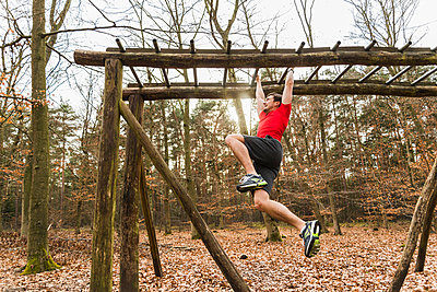 Young man brachiating on climbing frame - p300m1018980f by Uwe Umstätter